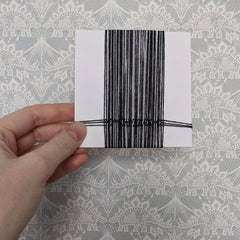 Card heavily wrapped with gray and black yarn vertically. There are three small horizontal yarns interwoven at the bottom of the card.