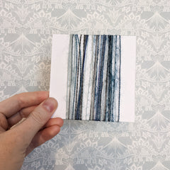 4 inch card vertically wrapped with a variety of blue and silver textured yarns.