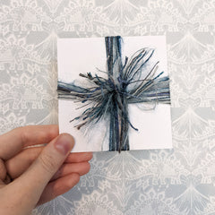 Card wrapped with blue and silver yarns, knotted in the center with fringe to create a poof.