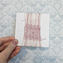 4 inch card wrapped and woven with pink and cream yarns.