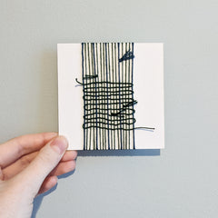 Card wrapped with dark green yarn, interwoven with knots and loops showing.