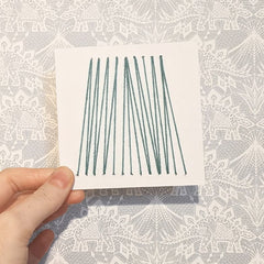4 inch card punched with holes and woven with pale green yarn in v shapes.