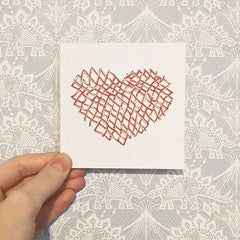 4 inch card punched with holes and cross stitched with pink and cream yarn in the shape of a heart.