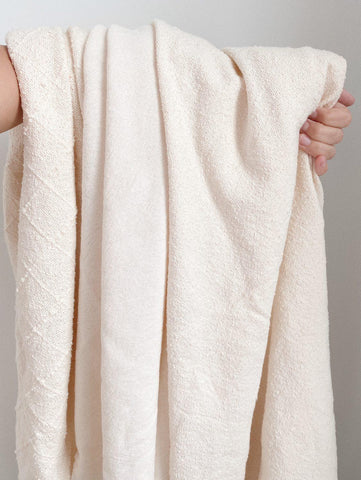 three organic cotton fabrics draped over an arm to show their light and texture