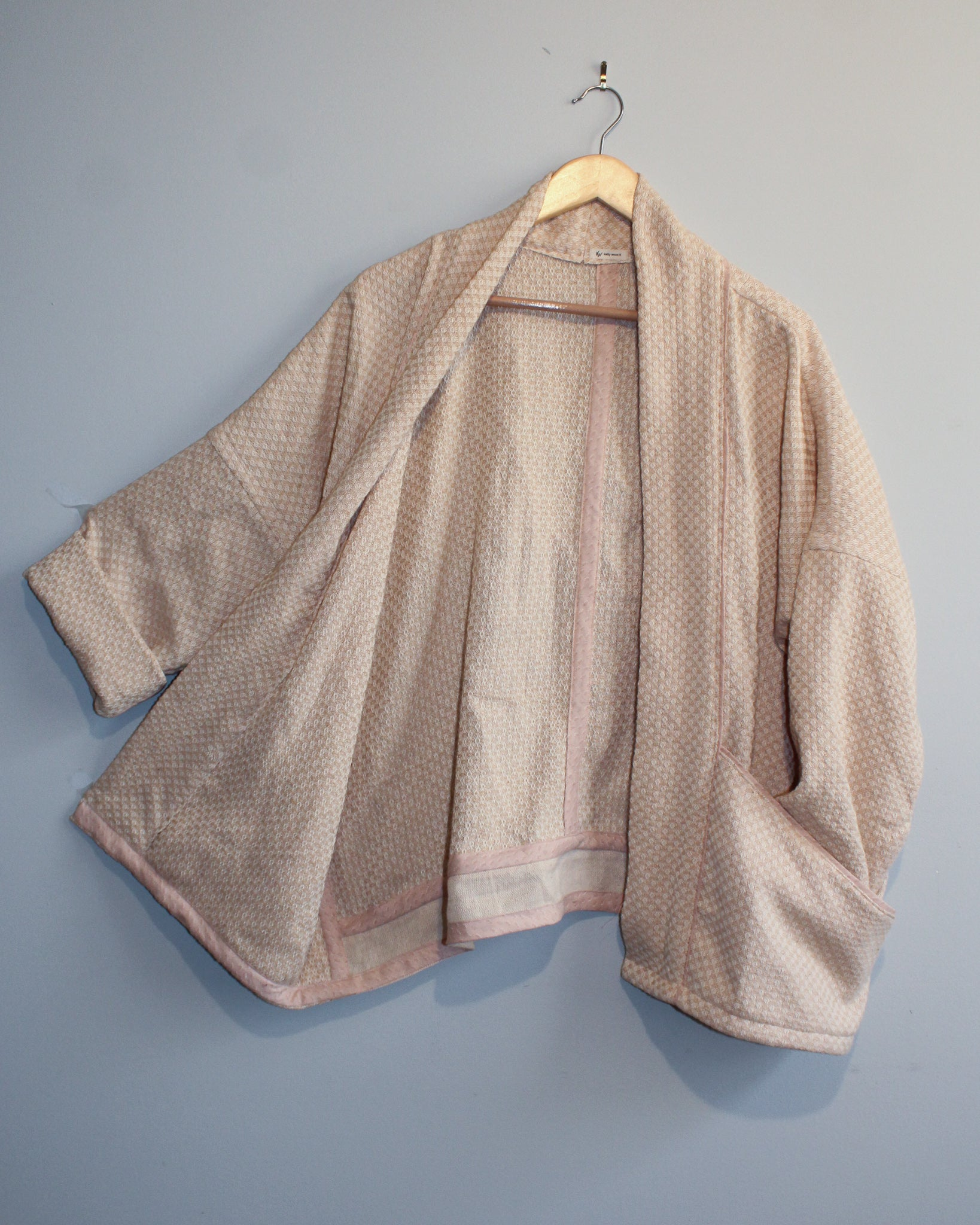 Photo of the full jacket, from the front hanging on a hanger.