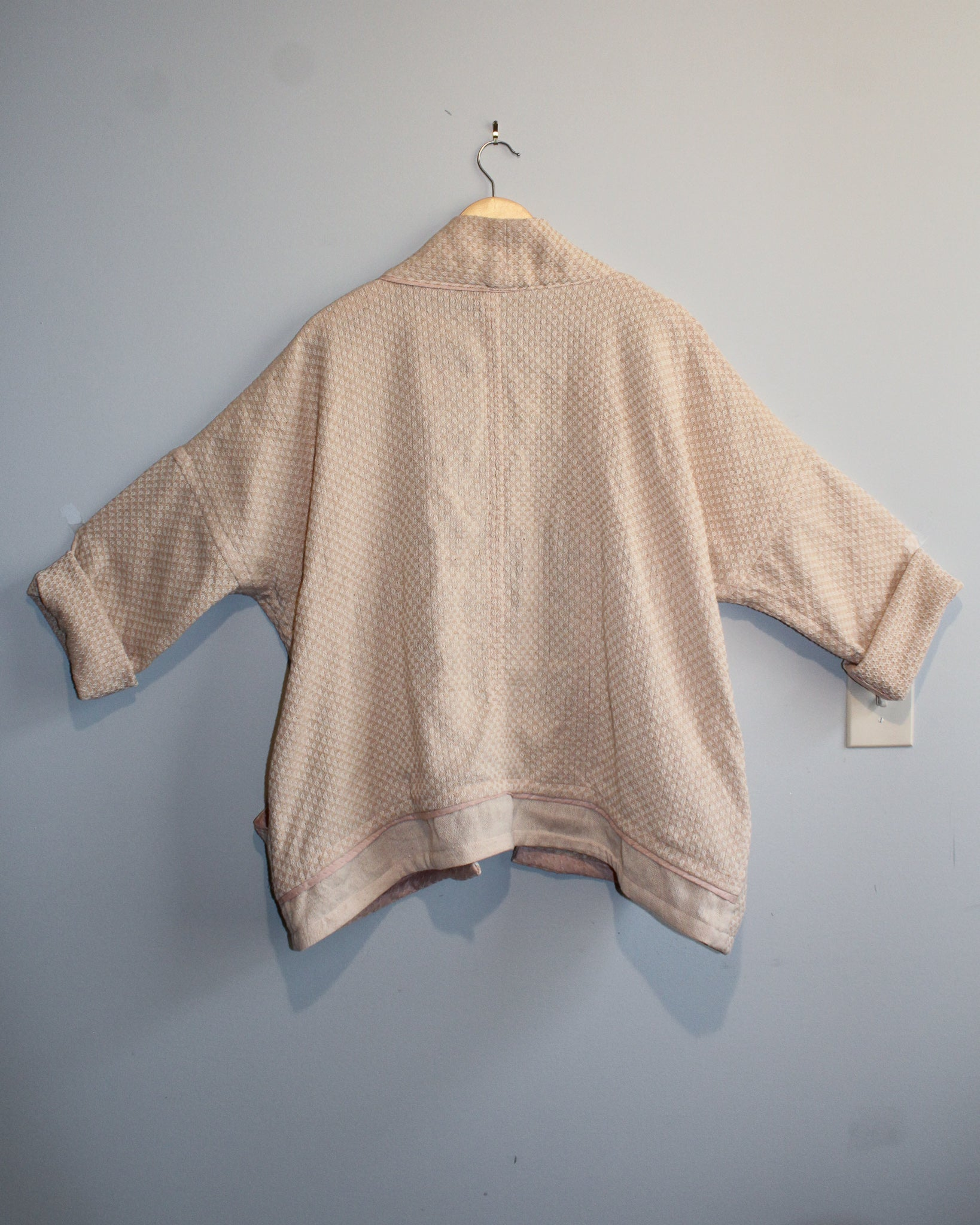 Photo of the jacket from behind, on a hanger.