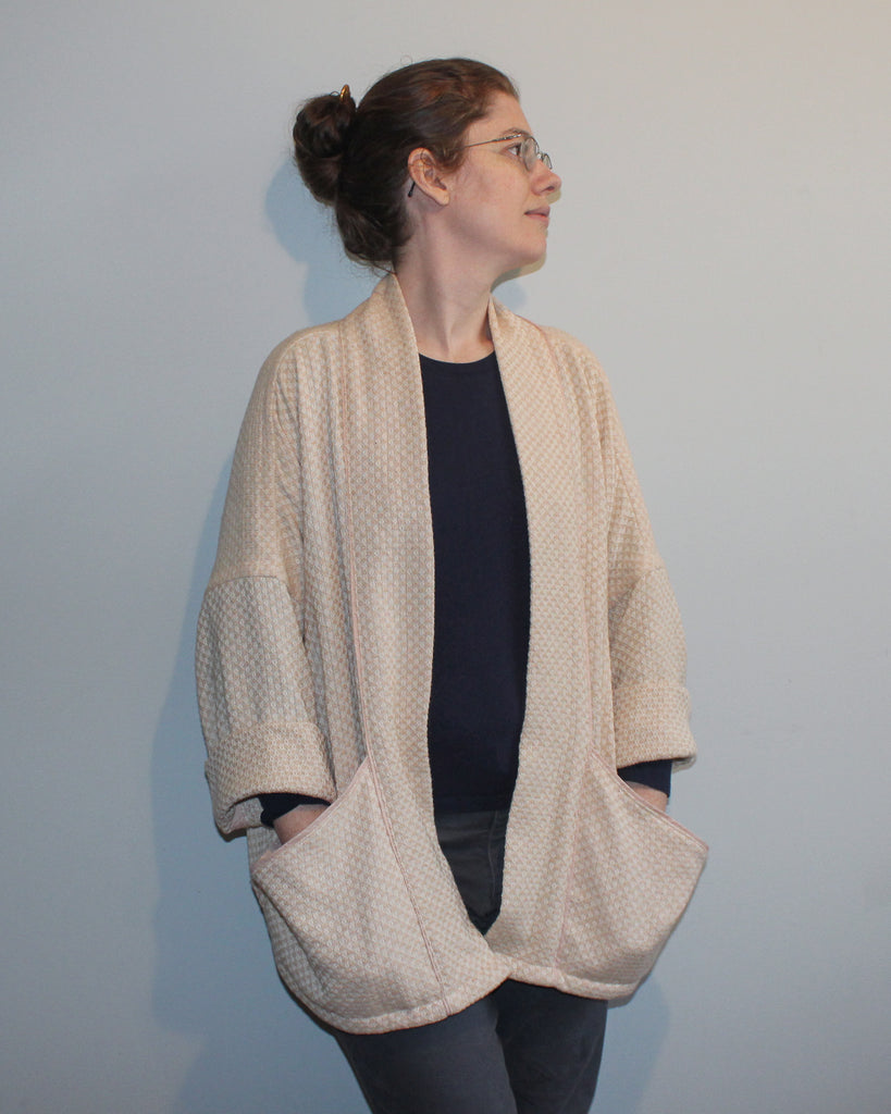 Girl wearing the jacket, sleeves partly rolled up, hands in pockets.