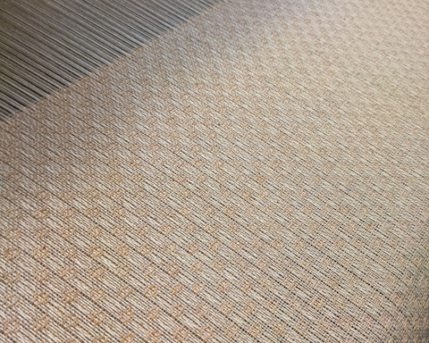 close up of cream and peach fabric on a loom.