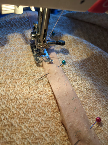 Image of fabric on a sewing machine, with bias tape pinned in place.