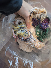 Image of a hand holding a a handful of multi color yarn scraps.