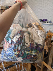 Large plastic bag full of multi colored yarn scraps.