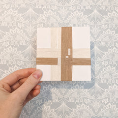 A 4 inch square card wrapped with overlapping strands of yarn in cream and tan.
