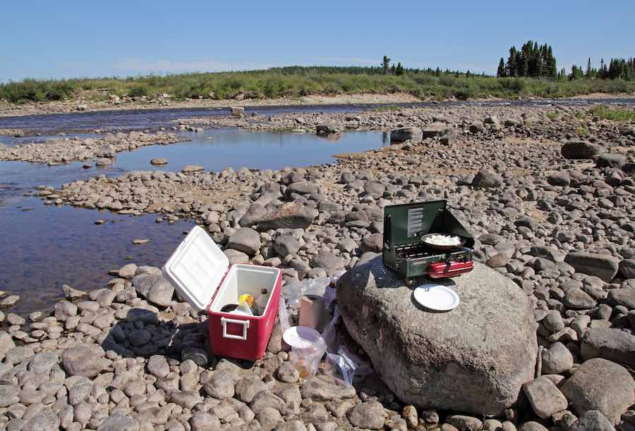 Keeping Food Cool While Camping: Cooler and A Stove on Rocks