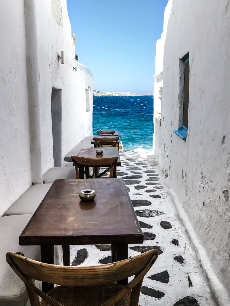 Prettiest alleys of Mykonos and best waterfront dining and bar for sunset drinks.  Kastros in Mykonos Town, Greek Islands.