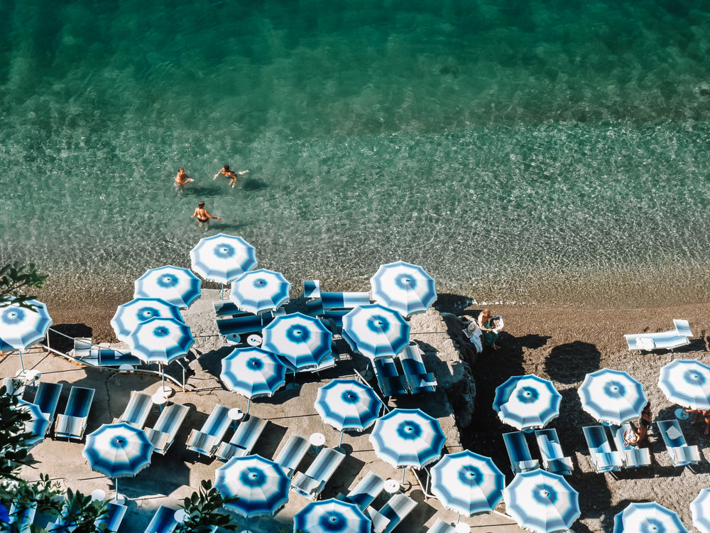 Positano beach on the Amalfi Coast Italy . European summer and long hot summer beach days under striped parasols and refreshing swims in the Mediterranean sea.