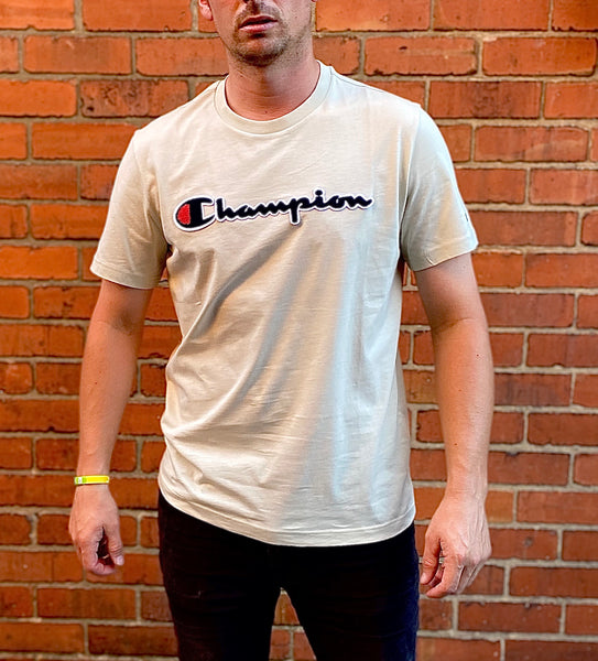 Cream Champion round-neck tee shirt with black embroidered logo across chest and C logo on sleeve