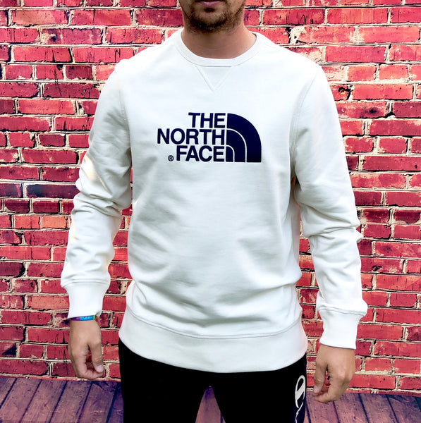 Thick, cream, round-neck, The North Face jumper, with large, embroidered, North Face logo on the chest in navy, and small printed logo on the reverse shoulder