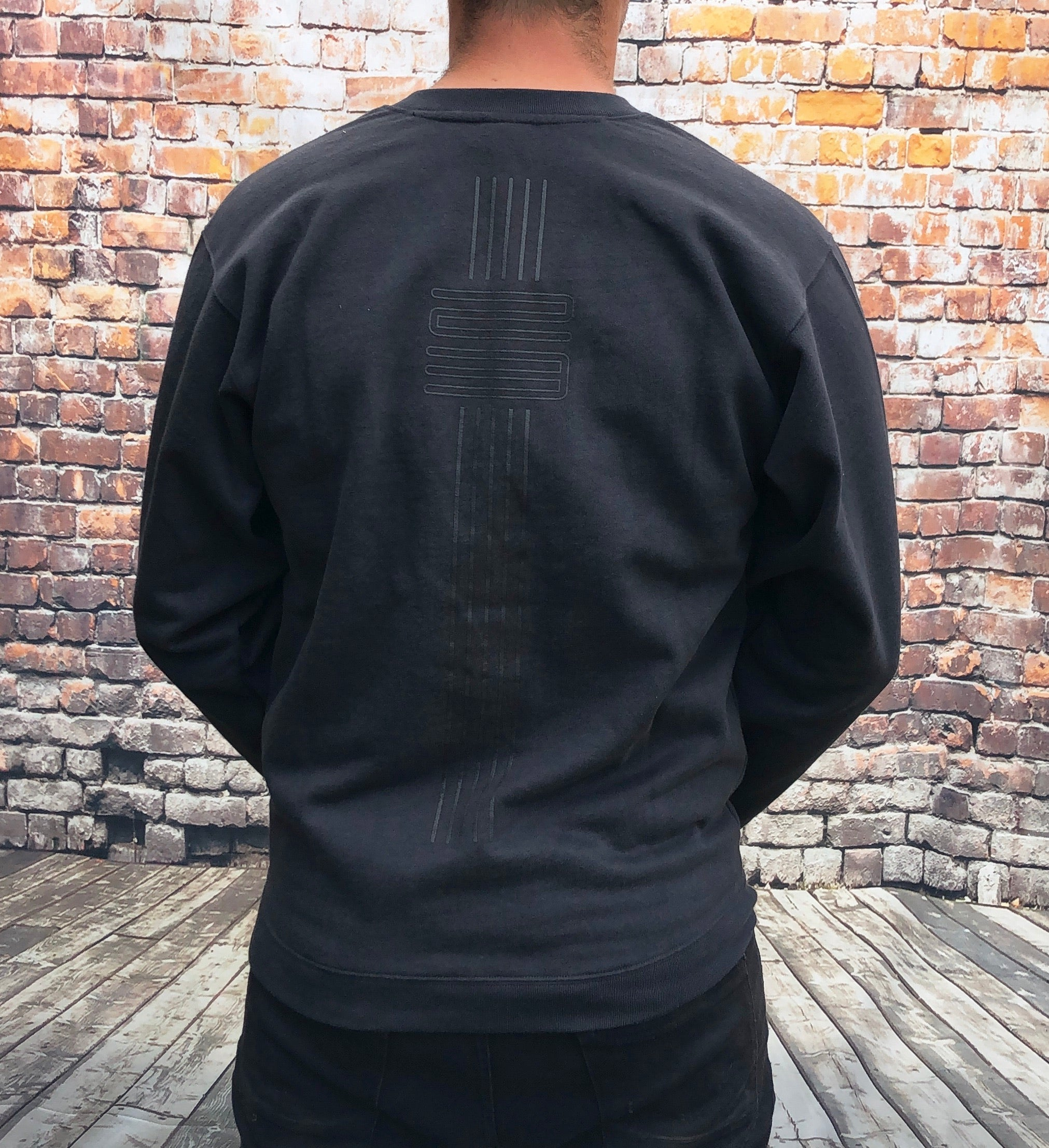 Black, thick, V-neck Nike jumper, with large, printed Nike basketball logo on the chest and trims down the back