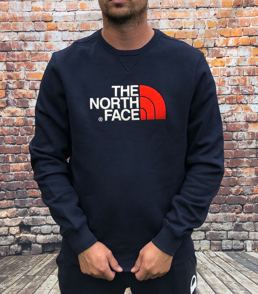 Thick, navy, round-neck, The North Face jumper, with embroidered, large North Face logo on the chest in white and red and small embroidered logo on the reverse shoulder