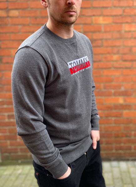 Grey Tommy Hilfiger Spellout jumper / sweater with Tommy Jeans Co USA embroidered across the chest and Tommy logo on the end of the sleeve