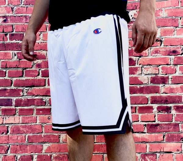 White Champion sports Bermuda-style shorts with small, embroidered logo on the thigh and black waistband and trims