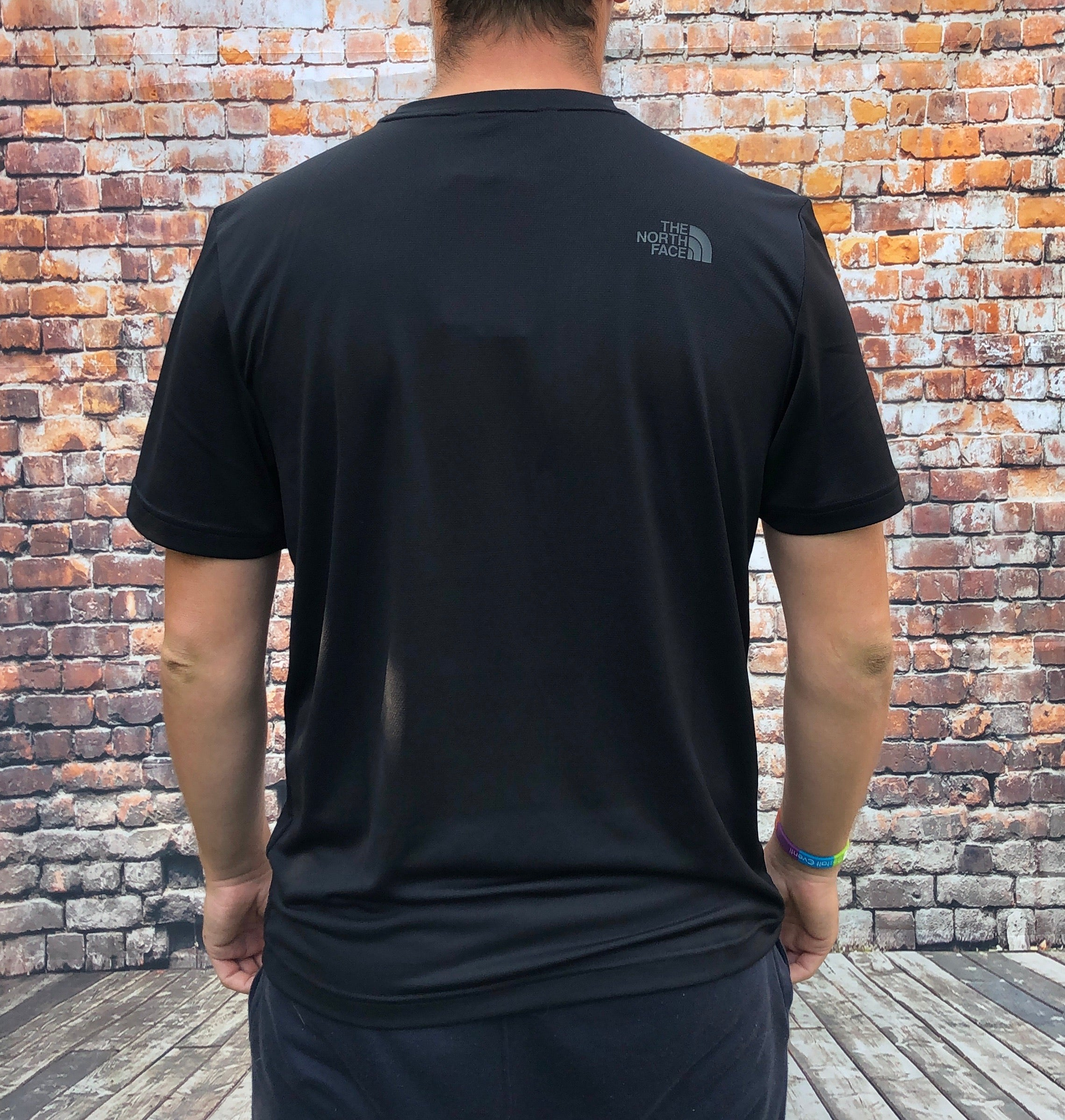 Black, round-neck, The North Face, sports tee shirt with a large, silver, printed logo on the chest and small logo on the reverse shoulder