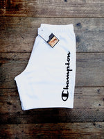 White Champion sports Bermuda-style, cotton shorts with large, printed lettering down the thigh in shiny black, and white drawstring