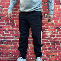 Black, thick fitted Nike jogging bottoms, with drawstring, white trim down the calves and white Nike embroidered swoosh below one of two pockets