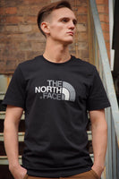 Black, round-neck, The North Face, soft, tee shirt with a large, silver and white, printed logo on the chest and small logo on the reverse shoulder