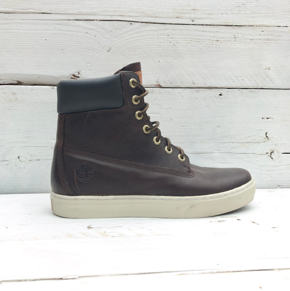 Pair of brown Timberland high-top boots with metal lace eye holes, Timberland logo on the tongue, black softened ankles and white soles
