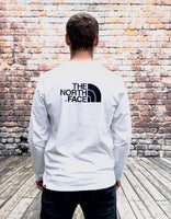 White, round-neck, The North Face, long-sleeved tee shirt with a small, printed, black North Face logo on the left of the chest and large, printed, black logo on the reverse