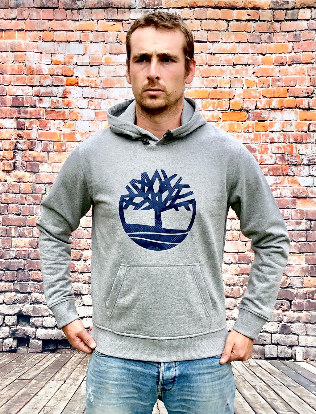 Grey thick, Timberland hoody / hooded jumper, with large, navy, printed Timberland logo on the centre chest and navy drawstrings