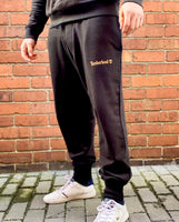 Black Timberland sports joggers, jogging bottoms with large, white, spellout logo, cuffed ankles and drawstring