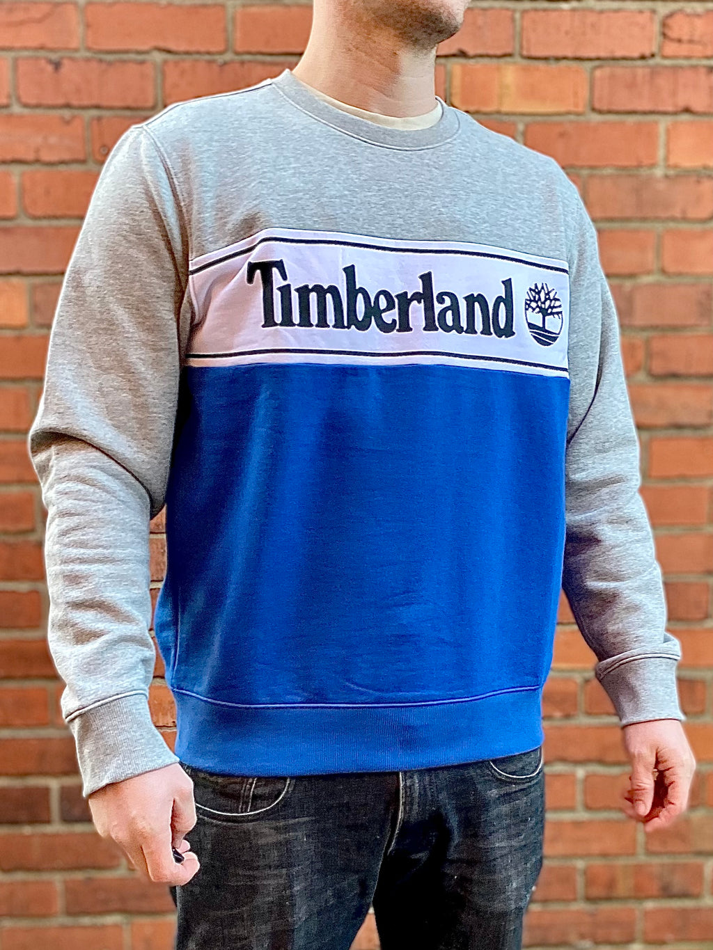 Grey and blue, thick, round-neck Timberland jumper, with white band across the chest and large, spellout, navy Timberland lettering