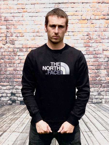 Thick, black, round-neck, The North Face jumper, with large, embroidered, North Face logo on the chest in white and silver, and small embroidered logo on the reverse shoulder
