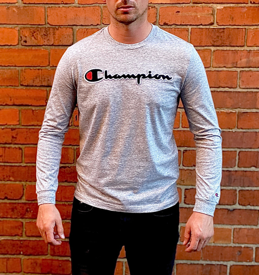 "Long-sleeved, round-neck tee shirt in grey, with large, spell-out Champion lettering embroidered across the chest, and embroidered ""C"" logo on the bottom of the sleeve"