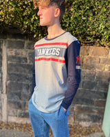 Grey long-sleeved Tshirt, with New York Yankees printed lettering in white and red stripes across the centre chest and red NY logo printed on the sleeve