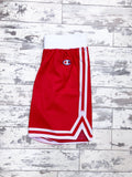 Red Champion sports Bermuda-style shorts with small, embroidered logo on the thigh and white waistband and trims