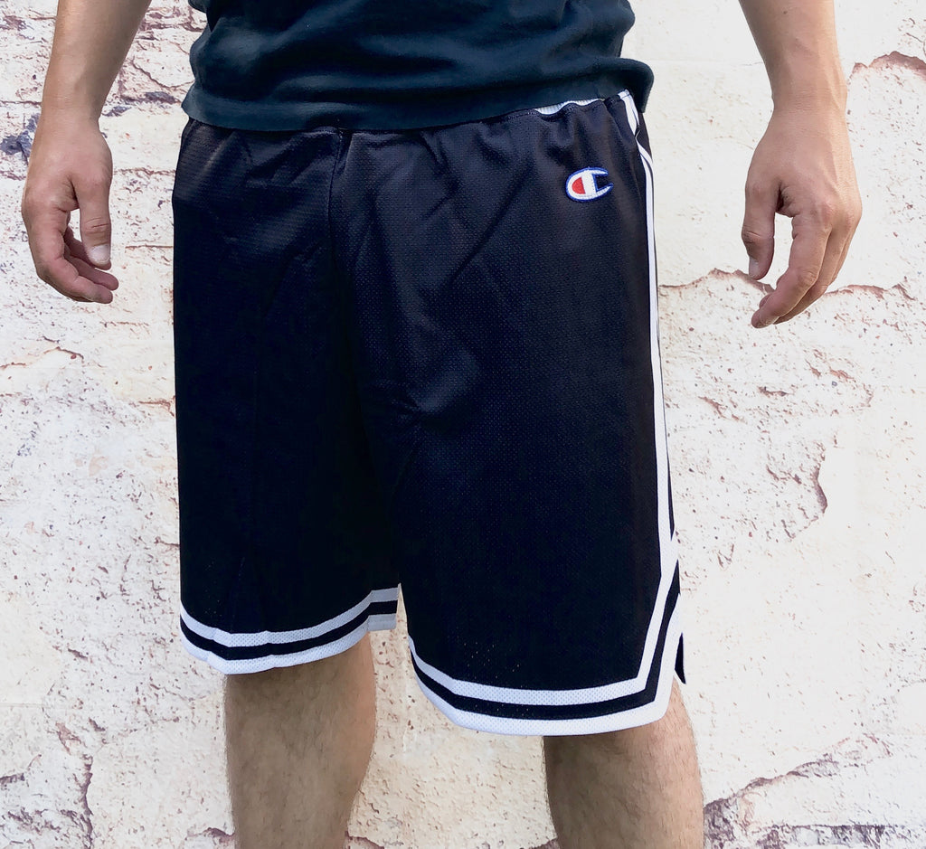 Black Champion sports Bermuda-style shorts with small, embroidered logo on the thigh and white waistband and trims