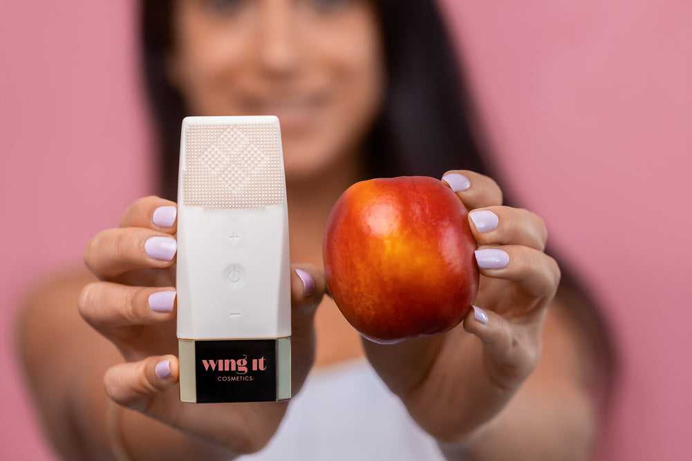 Gleam time facial cleansing brush being held next to a peach for peachy clean skin