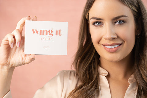 Model holding a box of wing it cosmetics lashes