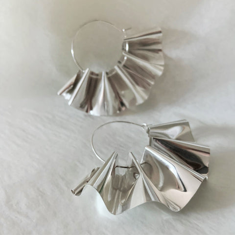 A pair of shiny silver rippled hoop earrings on a white background