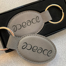 "Load image into Gallery viewer, ""Peace"" ambigram keychain"