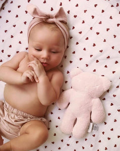 Baby lying down with headband on and teddy