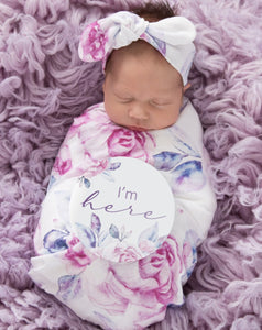 baby in a lilac swaddle with Im here sign