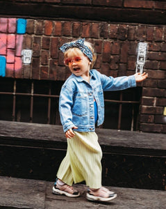 toddler in denim jacket walking with sunglasses and hedband