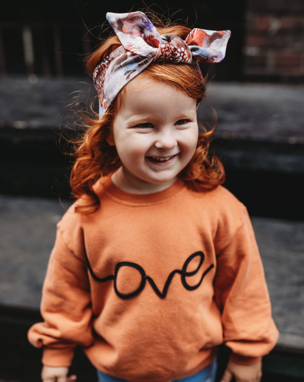 Girl in orange jumper and  headland