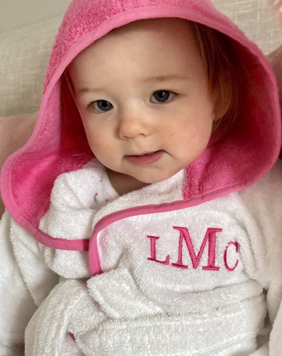 Baby in hooded pink dressing gown