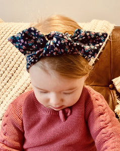 baby looking down in a navy headband