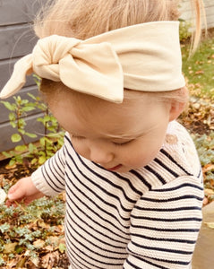 Toddler in garden in a cream headband